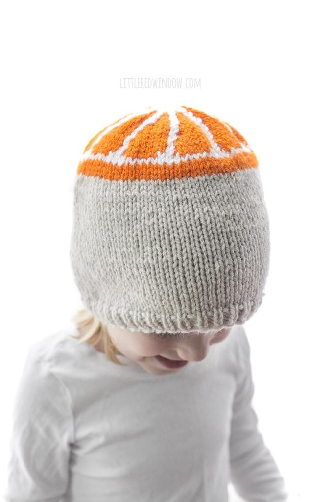 little girl wearing tan knit hat with orange slice pattern on the top looking down