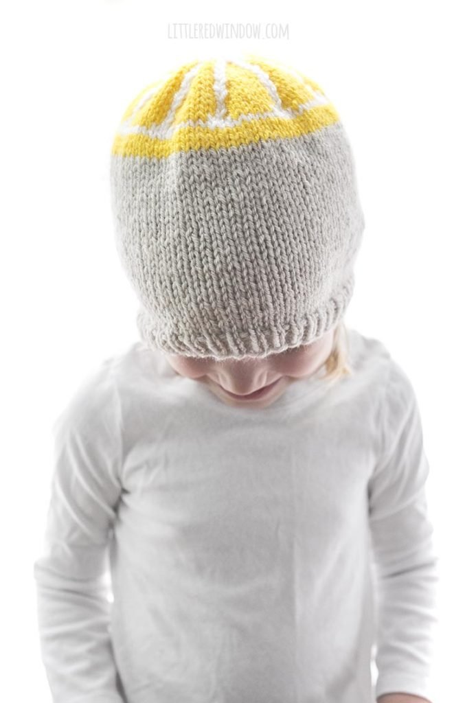 smiling girl looking down and wearing a tan knit hat with yellow lemon slice design on the top