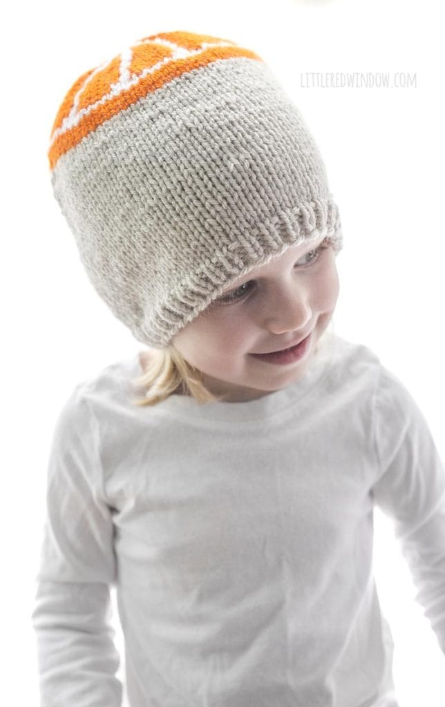 little girl wearing tan knit hat with orange slice pattern on the top looking down and to the right