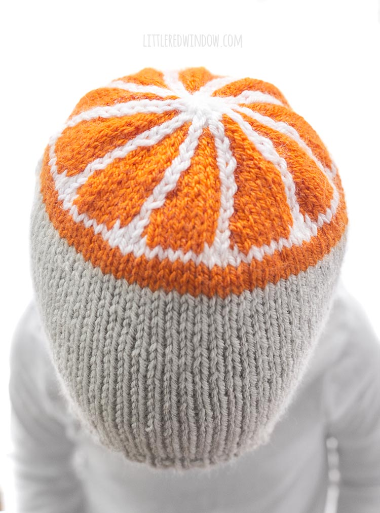 overhead view of little girl wearing tan knit hat with orange slice pattern on the top