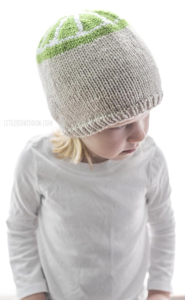 little girl wearing tan knit hat with green lime slice design on the top looking down and to the right