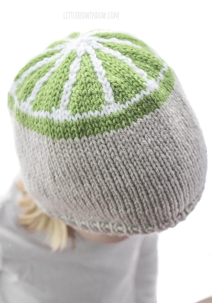 over head view of little girl wearing tan knit hat with green lime slice design on the top