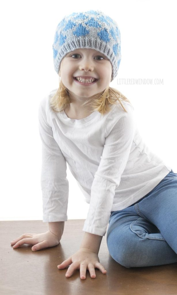 little girl in white shirt smiling and wearing blue knit hat with raindrops on it