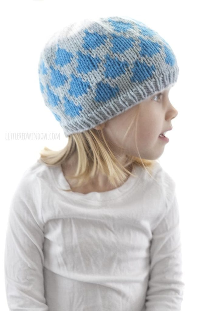 little girl wearing light blue knit hat with blue raindrop pattern and white cloud on top look off to the right