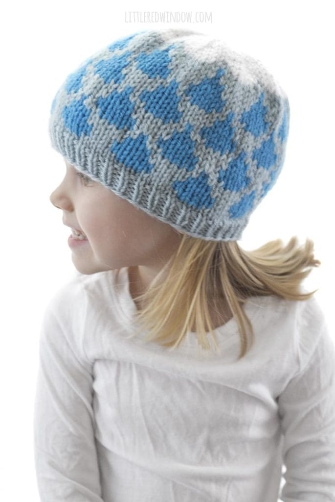 little girl wearing light blue knit hat with blue raindrop pattern and white cloud on top look off to the left