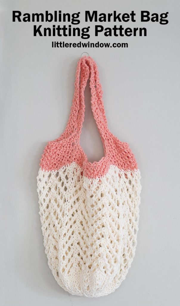 cream and coral lace knit market bag hanging on a hook in front of a gray wall