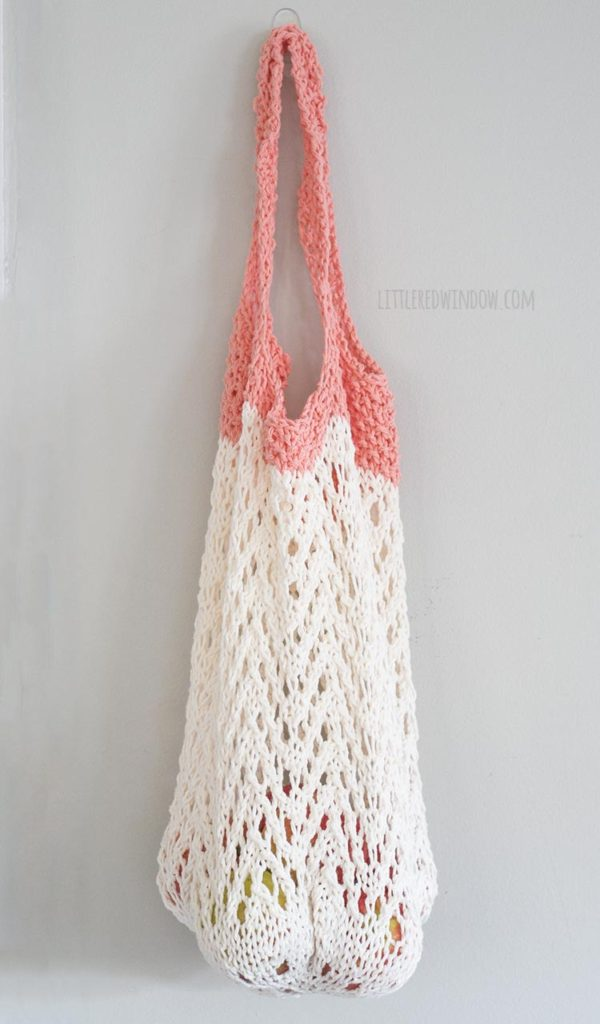 cream and coral lace knit market bag filled with apples hanging on a hook in front of a gray wall