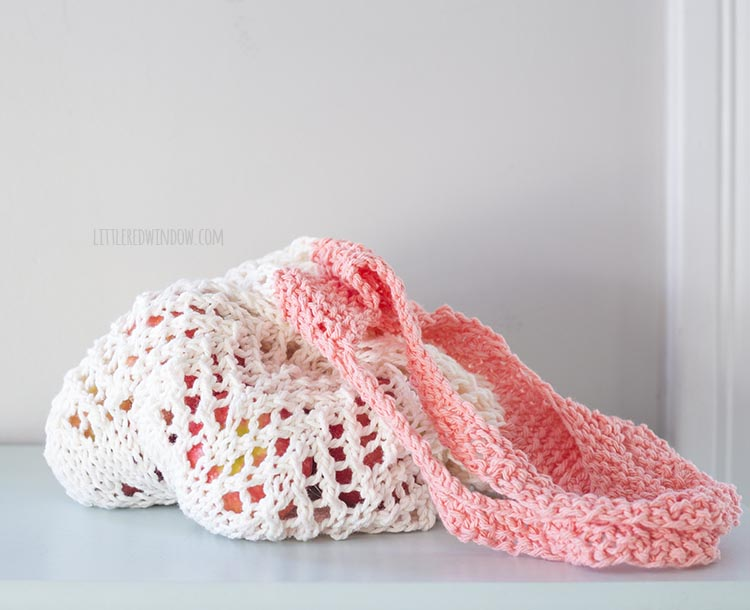 cream and coral lace knit market bag filled with apples sitting on a blue table