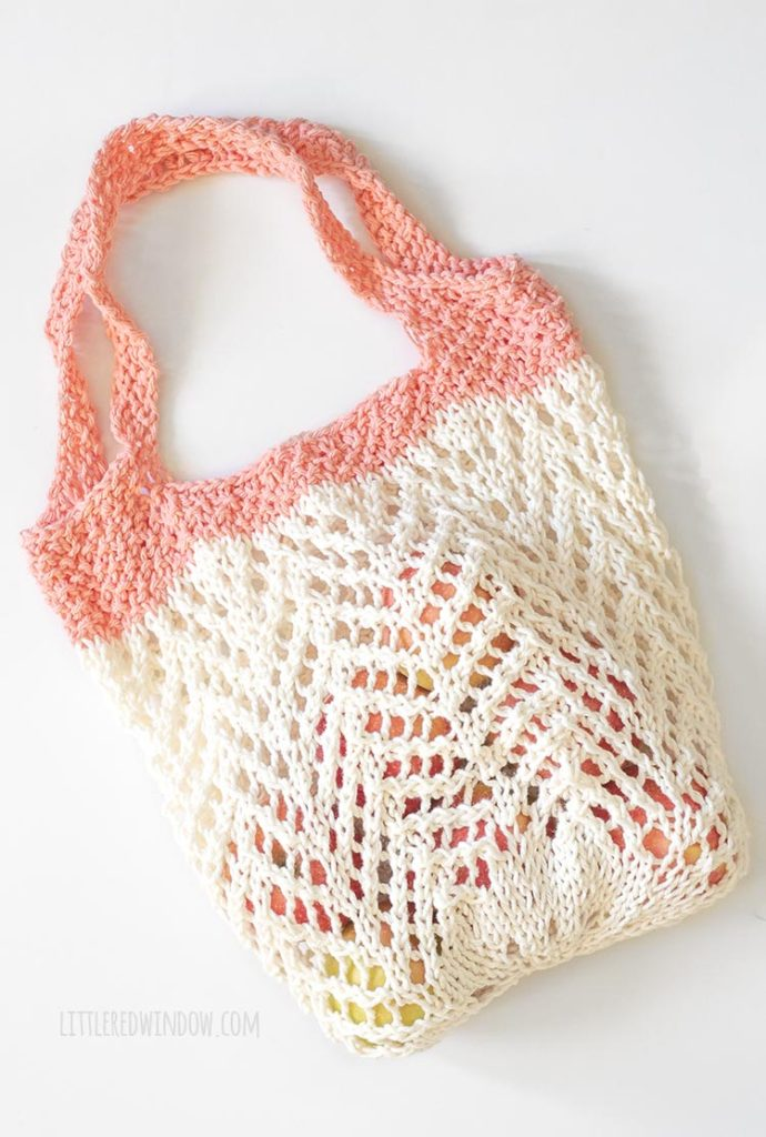 cream and coral chevron lace knit market bag filled with apples laying flat on a white floor
