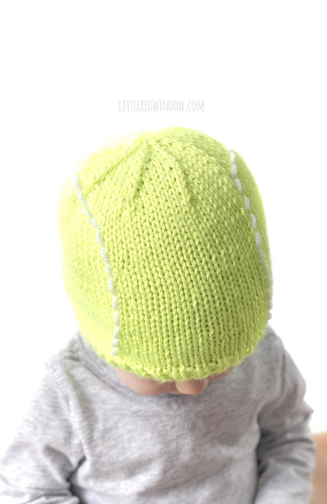 top view of baby wearing green tennis ball hat