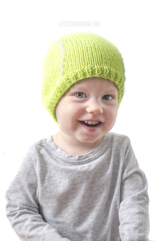 smiling baby in gray shirt wearing bright green tennis ball hat