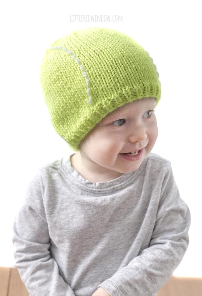 cute baby in gray shirt looking off to the right and wearing a bright green tennis ball hat