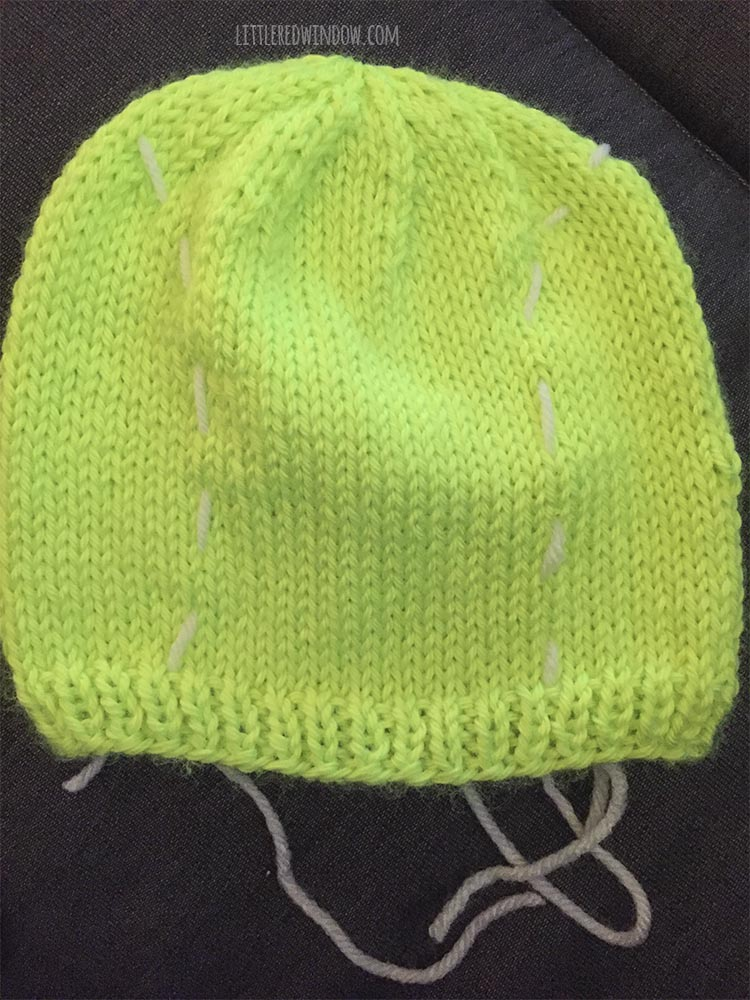 bright green tennis ball hat withtwo lines of white basting stitches