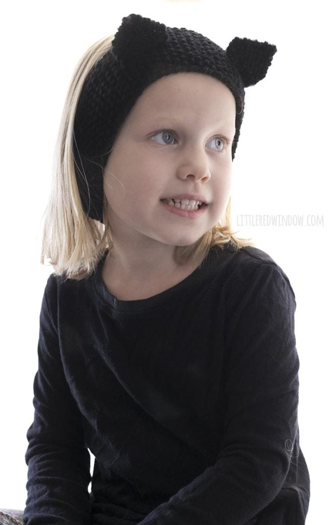 little girl wearing knit black cat headband and looking down and to the right