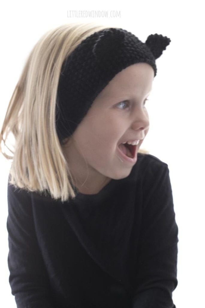 little girl wearing knit black cat headband and looking off to the right and laughing
