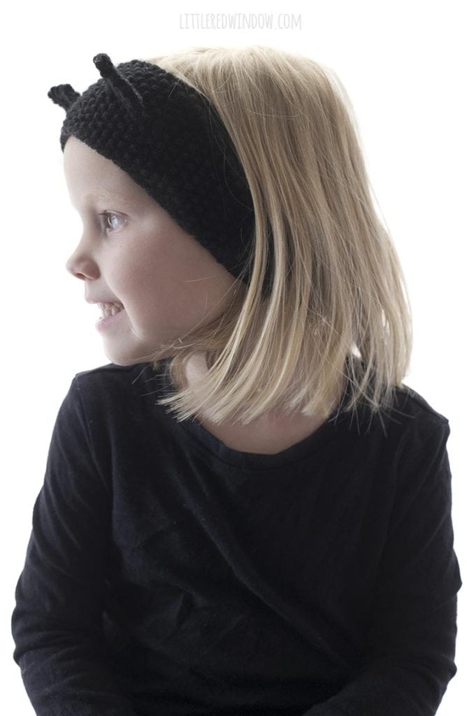 little girl wearing knit black cat headband and looking up off to the left