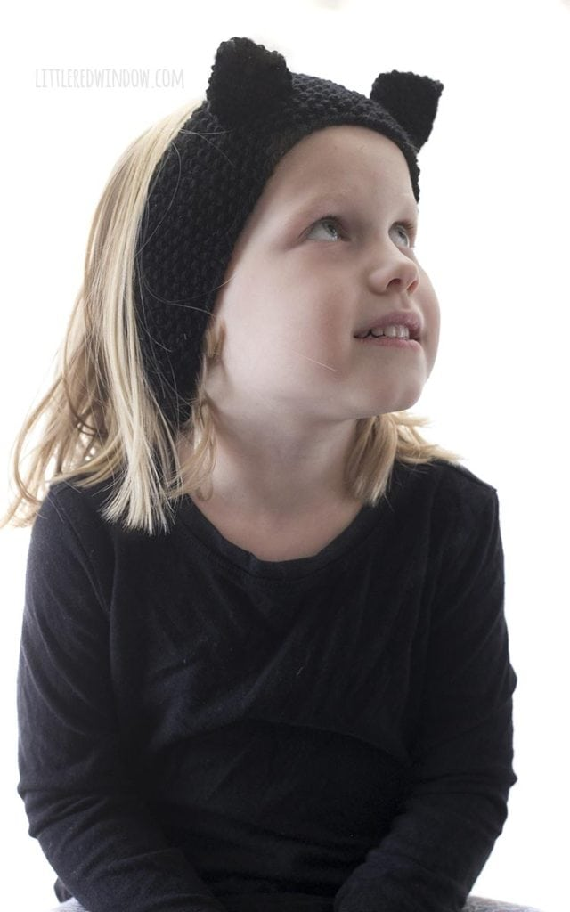 little girl wearing knit black cat headband and looking up and to the right