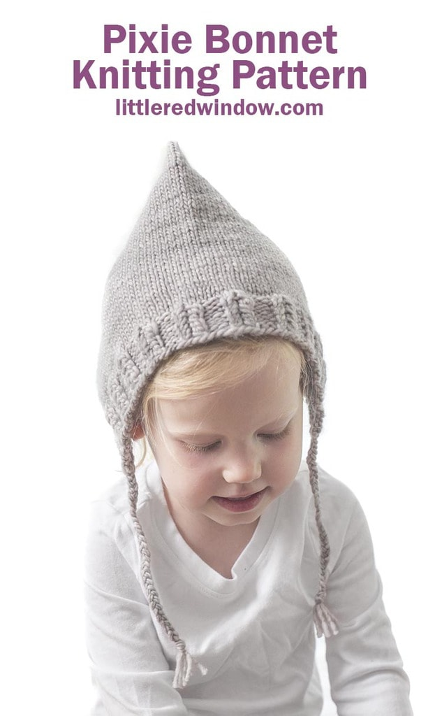 toddler in white shirt wearing tan pointed knit pixie bonnet with braided ties and looking down