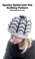 small girl in black shirt wearing white knit hat with spiderweb and spider on it