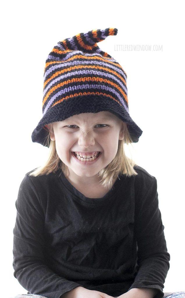 garota fazendo cara de bruxa rindo e usando chapéu de bruxa listrado