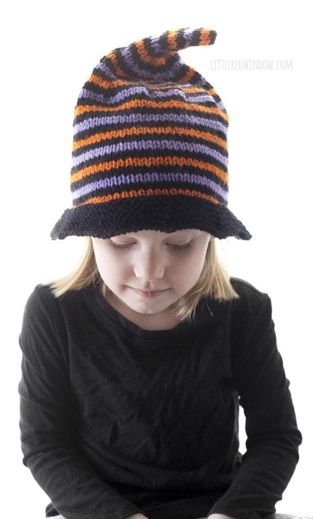 vista frontal de uma menina em uma camisa preta usando um chapéu de bruxa listrado de malha laranja preta e roxa