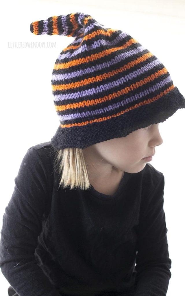 menina usando chapéu de bruxa de malha de halloween com listras pretas e roxas laranja e olhando para baixo e para a direita