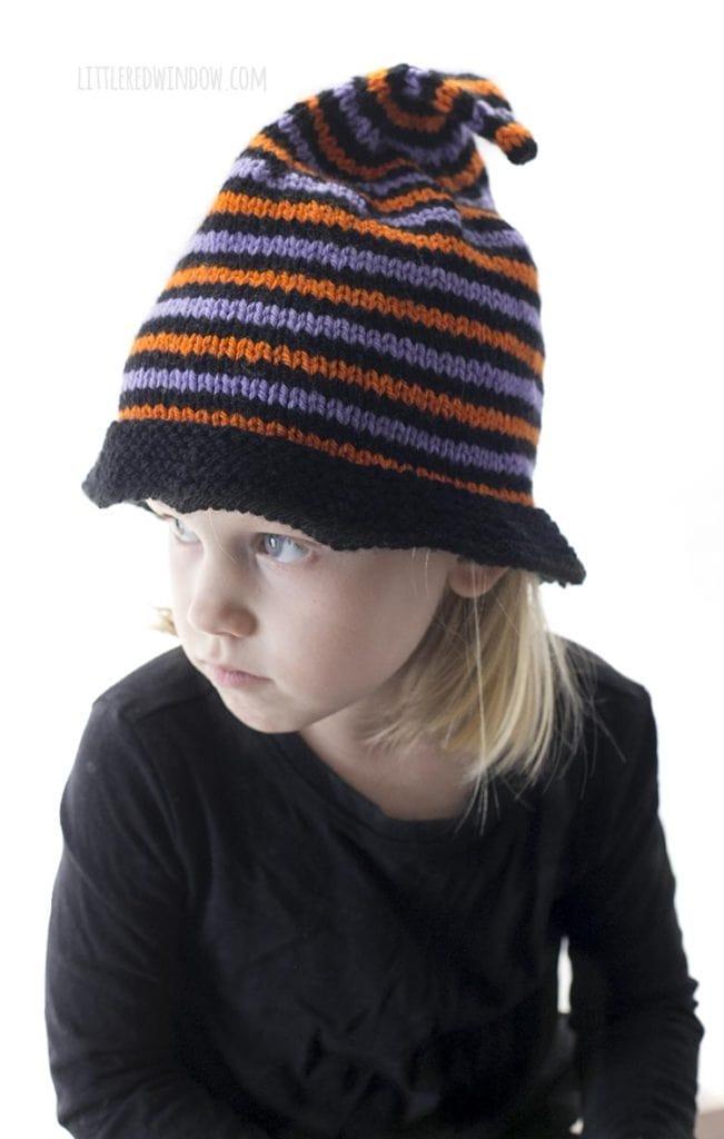 menina usando chapéu de bruxa de malha de halloween com listras pretas e roxas laranja e olhando para a direita