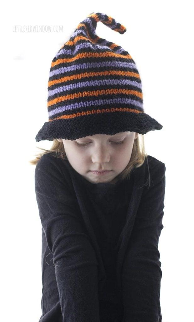 menina de camisa preta encolhendo os ombros e usando chapéu laranja de bruxa listrado de roxo e preto