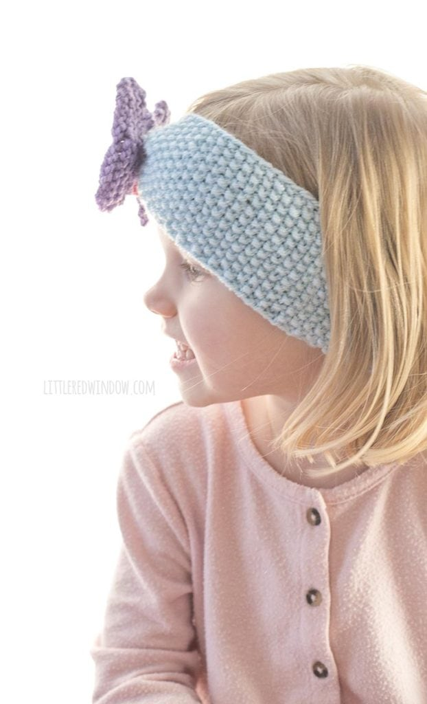 side view of little girl in pink shirt wearing blue knit headband with purple butterfly on the front