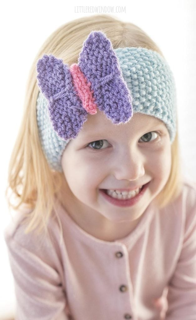 Closeup of girl smiling and wearing blue knit headband with purple and pink butterfly on the front
