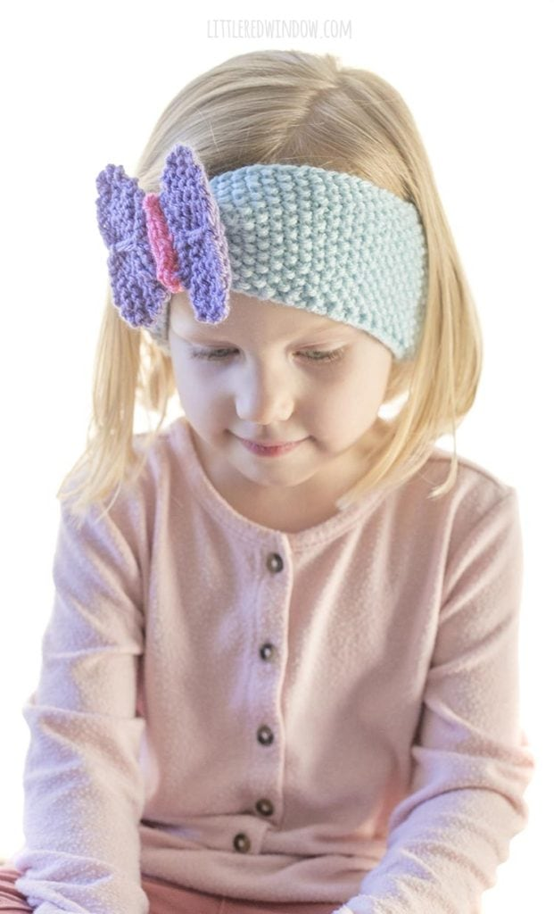 little girl in pink shirt wearing blue knit headband with purple butterfly on the front looking off to the right
