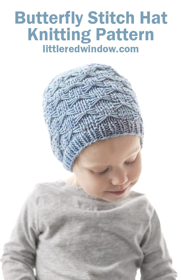 smiling little girl looking down and wearing a light blue knit hat with butterfly stitches all over it