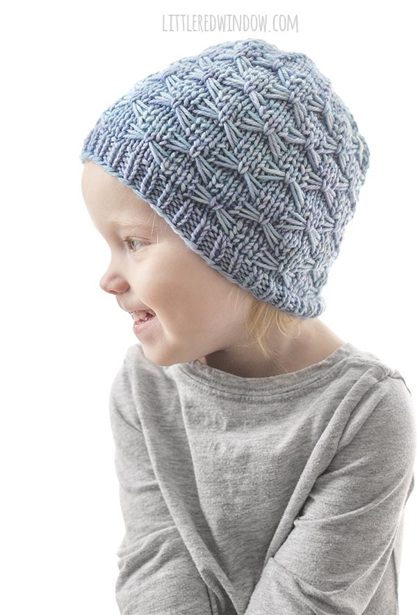 smiling girl in gray shirt looking off to the left and wearing light blue butterfly stitch hat