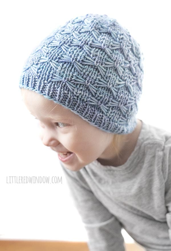 girl laughing and leaning over to the left whitle wearing gray shirt and light blue knit hat with butterfly stitches on it