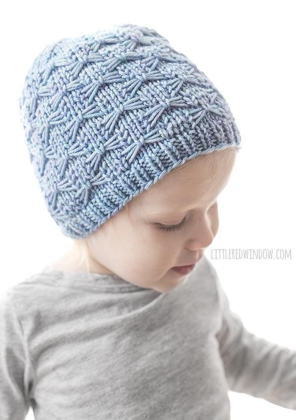 girl looking down and to the right in gray tshirt and light blue butterfly stitch hat