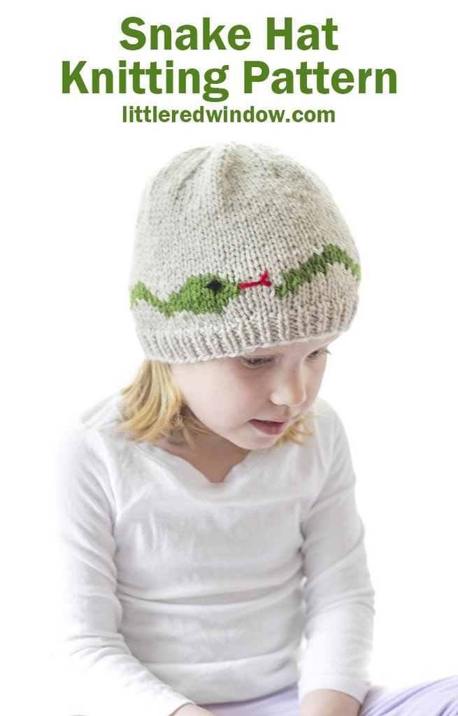 little girl in tan knit hat with a green snake around the middle