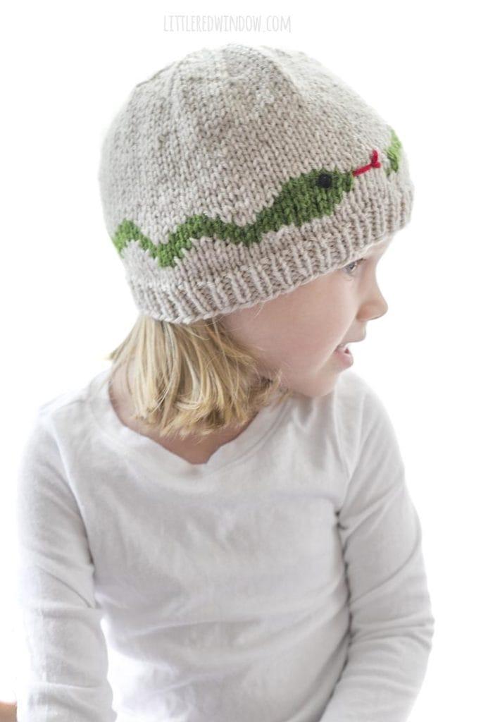 vista lateral de menina usando padrão de tricô de chapéu de cobra em bronzeado com uma cobra verde no meio