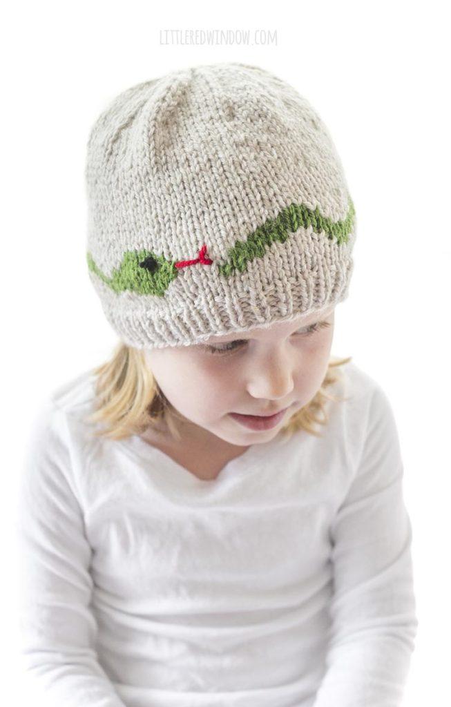 menina com camisa branca e chapéu de malha castanha com cobra verde com a língua bifurcada vermelha tricotada ao redor do centro, ela está olhando para baixo e para a direita