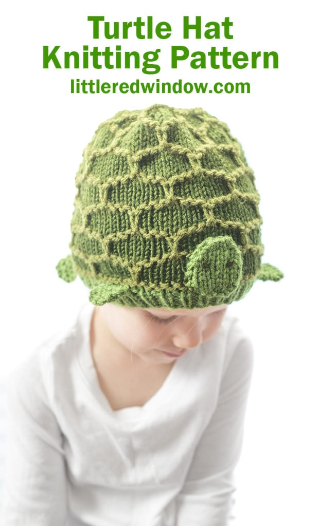 little girl looking down and wearing a green turtle hat