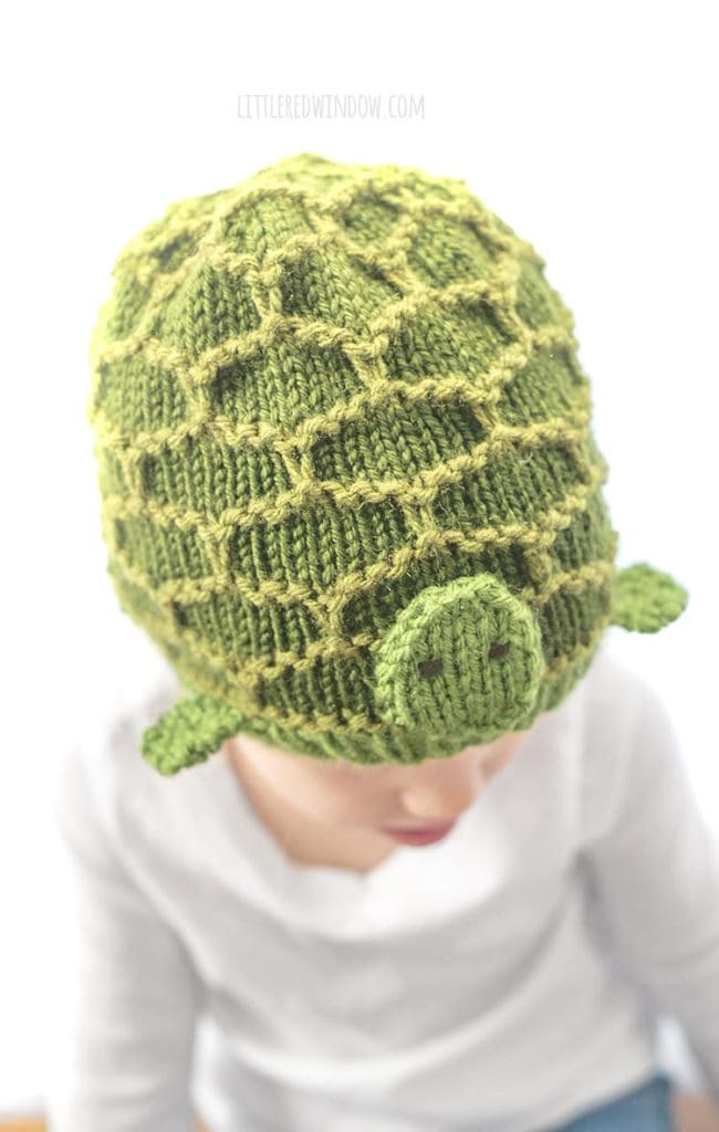 closeup of green turtle hat knitting pattern with hexagon pattern shell feet and a little face