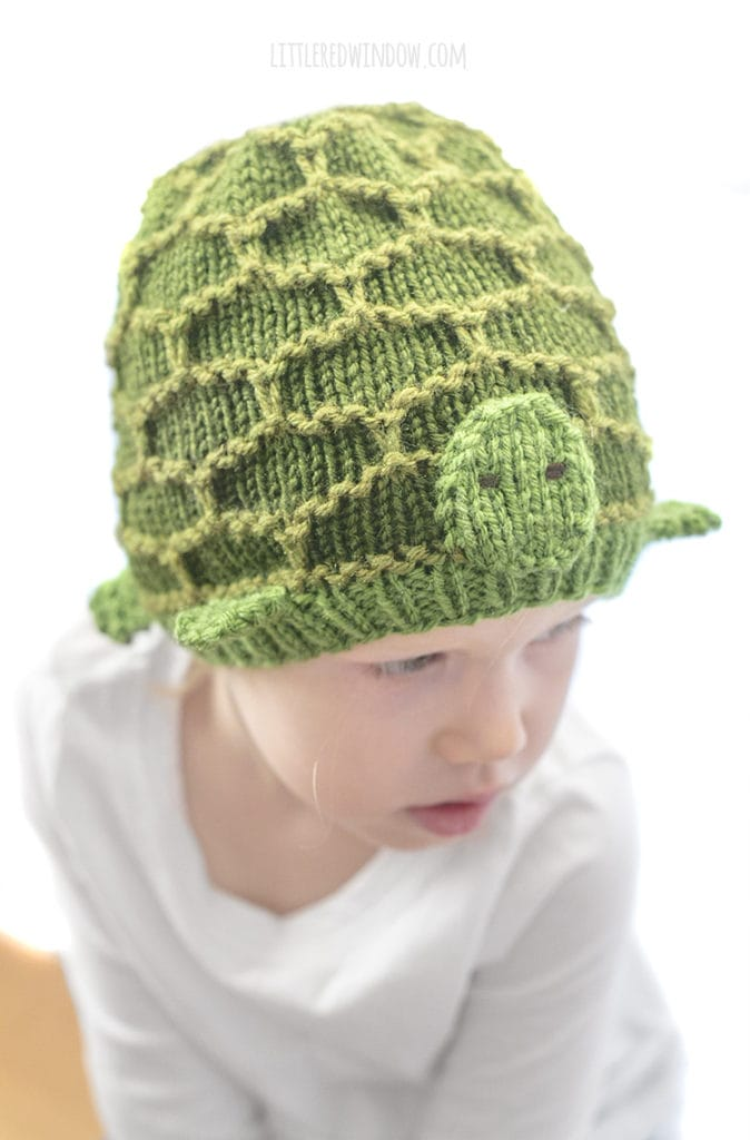 little girl wearing green turtle hat looking down an to the right