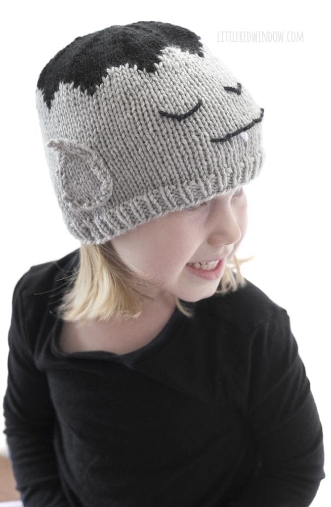 little girl wearing gray knit vampire hat with pointy vampire ears on the side
