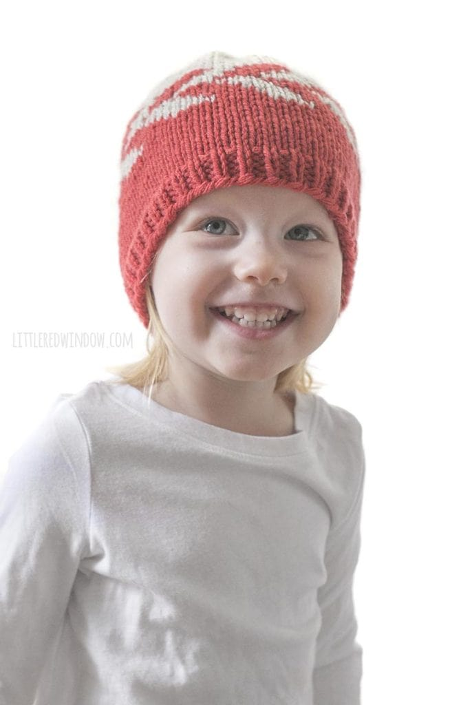 smiling girl wearing red and tan zipper hat looking up above the camera