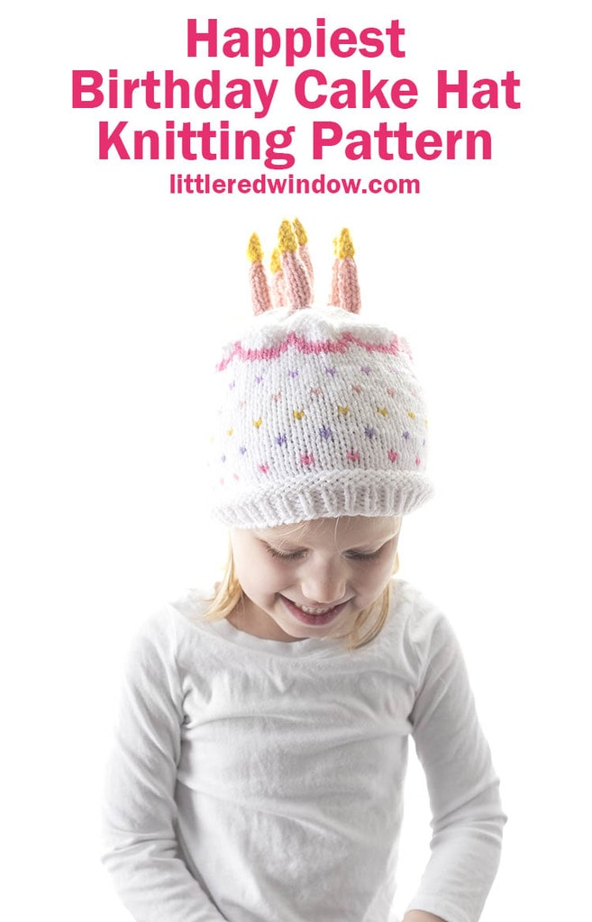 little girl in white shirt smiling looking down and wearing a knit hat that looks like a birthday cake with candles on top