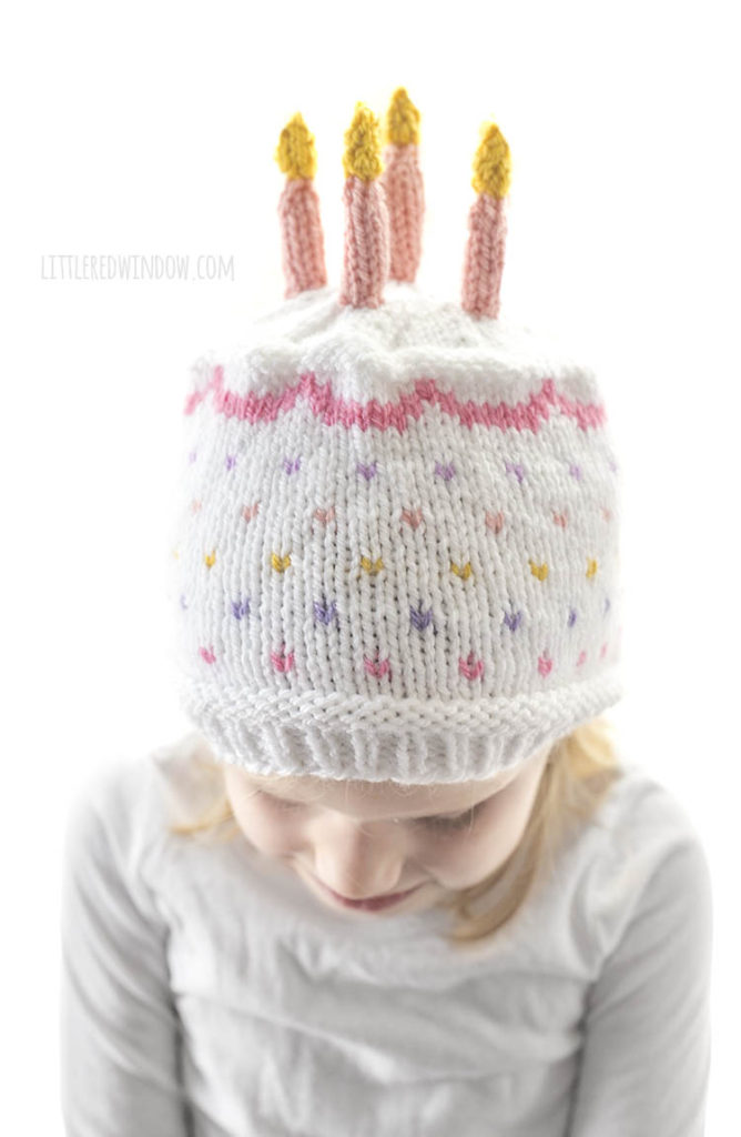 closeup of white knit birthday cake hat with rainbow sprinkles pink frosting and pink candles on top