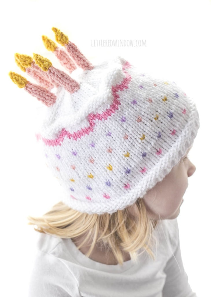 top view of white and pink birthday cake hat with pink knit candles on top