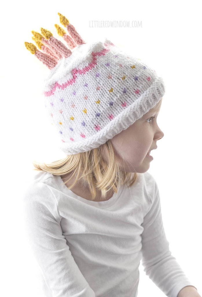 little girl wearing white and pink knit birthday cake hat looking off to the right