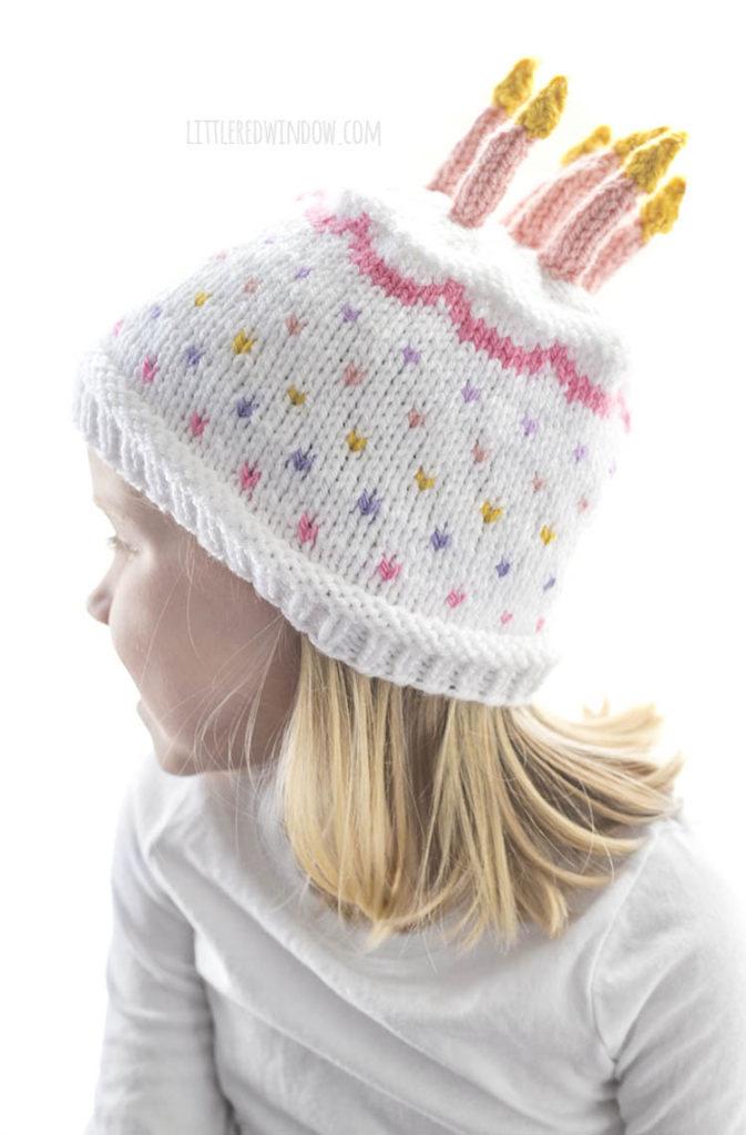 little girl wearing white and pink knit birthday cake hat looking off to the left