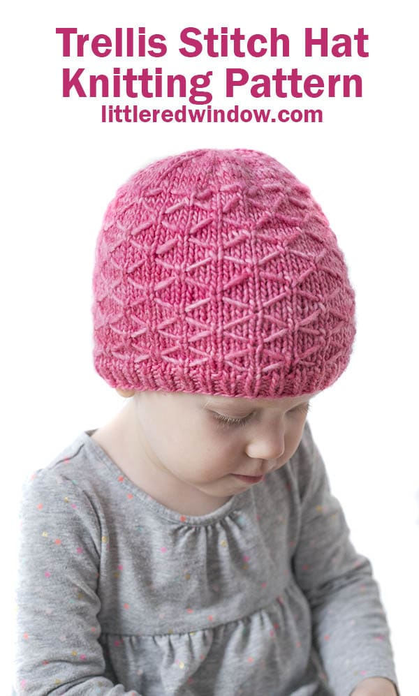 little girl in gray shirt wearing pink knit hat with diamond pattern on it