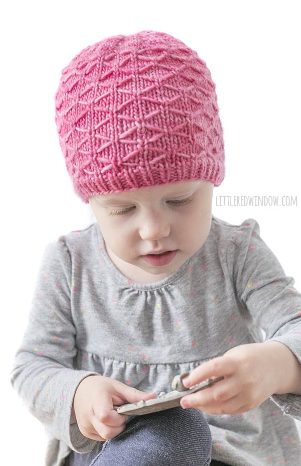 little girl examining something in her hands while wearing a pink knit hat with diamond trellis stitch pattern on it